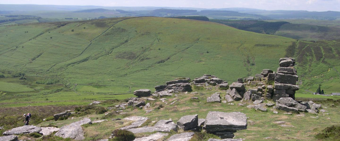 Grimspound, a late Bronze Age settlement, rock circles surrounded by a low stone wall.
